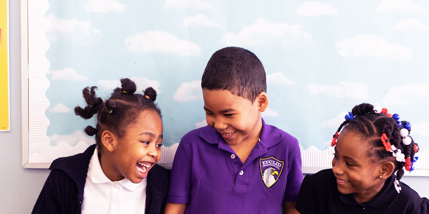Elementary students smiling and laughing in school hallway.