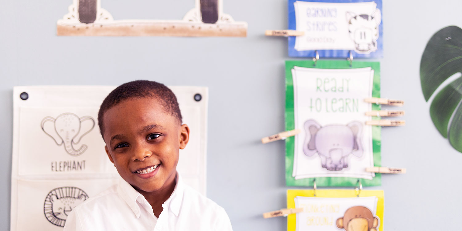 Smiling elementary student in a classroom.