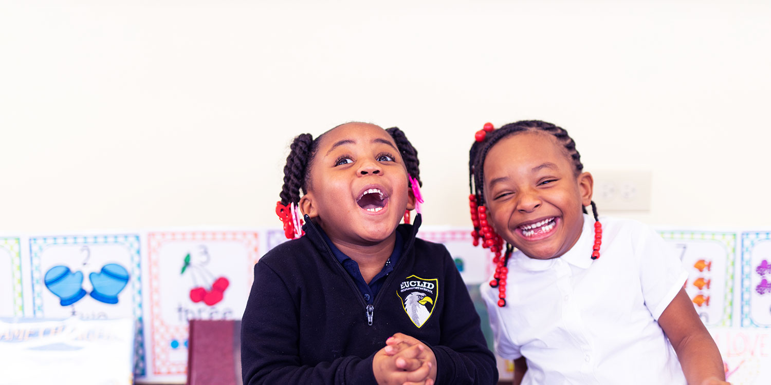 Smiling students next to each other in a classroom.